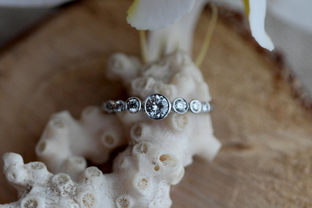 7 bezel diamond ring in white gold with feather detailing along the arms.