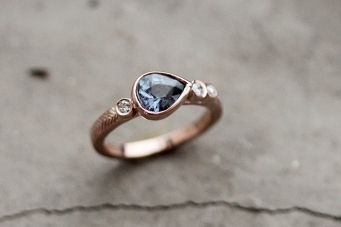 Custom rose gold engagement ring featuring a deep blue tear drop shaped gem and three bezel set diamonds in rose gold.