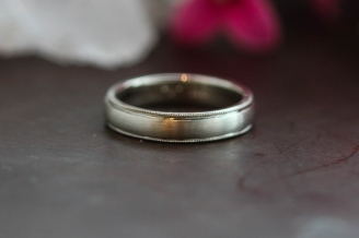 A low dome wedding band with a classic milgrain edge and a brushed finish