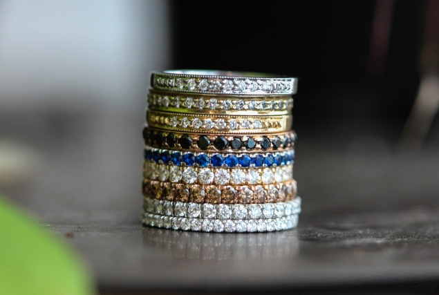 Pave wedding band stack featuring clear, cognac and black diamonds, and blue sapphires.
