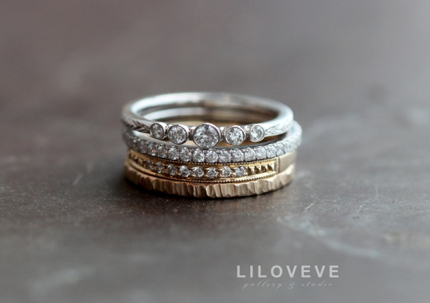 A dainty stack featuring the five bezel engagement ring, a pave diamond eternity band, our 8 diamond and beadwork band, and our bark texture wedding band.