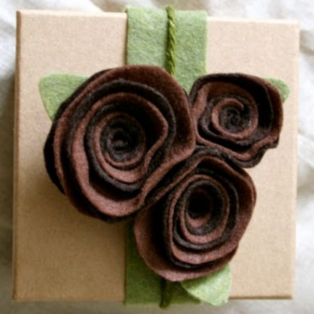 "Add felt decorations to your wrapping. Get fancy with a glue gun - make roses with a 1"" strip of felt and roll the bottom and glue and spread the ""petals"" out."