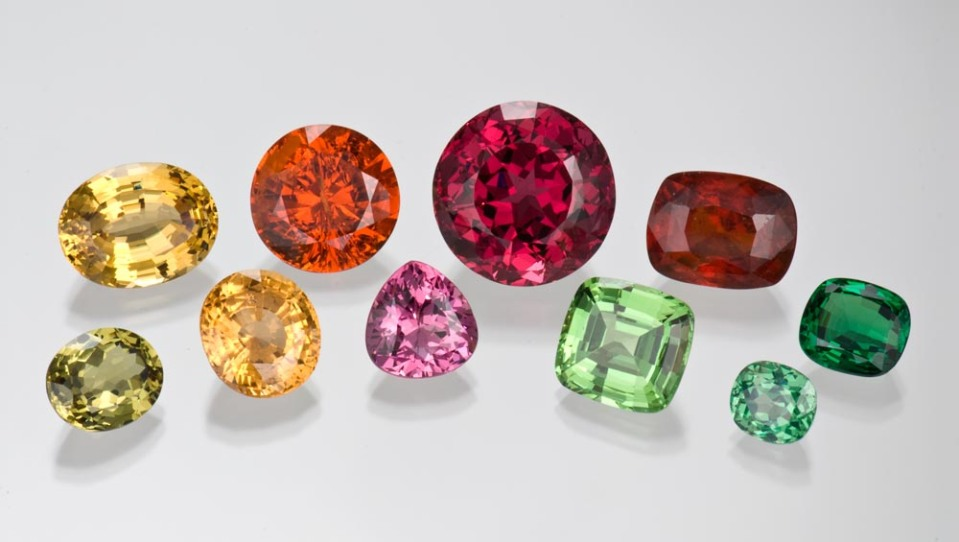 Photographed from the GIA Collection for the CIBJO project. Top row, left to right: 16.94 ct yellow oval garnet; 19.89 ct round orange spessartite garnet; 44.28 ct round, deep pink rhodolite garnet; 16.99 ct reddish orange cushion cut garnet; and 7.26 ct cushion cut tsavorite garnet. Bottom row, left to right: 8.20 ct oval greenish yellow garnet; 12.36 ct oval golden yellow garnet; 9.22 ct pink pear cut garnet; 14.53 ct light green cushion cut grossular garnet and 4.32 ct bluish green cushion cut garnet.